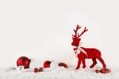 圣诞节装饰:在木白色背景的红色驯鹿 免版税图库摄影