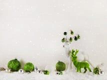 圣诞节装饰:在木白色背景的绿色驯鹿 免版税图库摄影