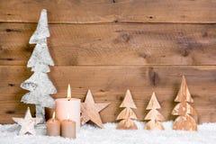 圣诞节装饰:木树、星、蜡烛和雪在木头 免版税库存照片