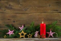 圣诞节装饰:红色蜡烛和早午餐在木老后面 库存图片