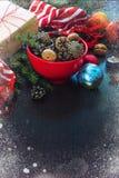圣诞节装饰-充分红色碗冷杉锥体,在牛皮纸包裹的礼物盒,杉木分支,对光检查,坚果,茴香,苹果, ch 免版税库存图片