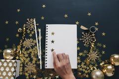 圣诞节计划概念嘲笑 妇女手在黑背景washi磁带,金子上的组织笔记本担任主角五彩纸屑, serpenti 免版税图库摄影
