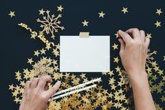 圣诞节计划概念嘲笑 妇女手组织地方 关于黑背景的笔记与washi磁带,金子担任主角五彩纸屑, 免版税库存图片