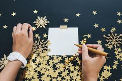 圣诞节计划概念嘲笑 有wath文字笔记的妇女手关于与washi磁带,金子的黑背景担任主角五彩纸屑, s 库存照片