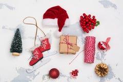 圣诞节设置与圣诞老人帽子,礼物盒,在白色xmas背景滑冰 库存照片
