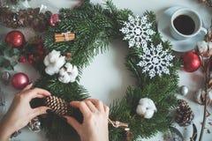 圣诞节诗歌选用女性手,锥体,常青树 免版税库存图片