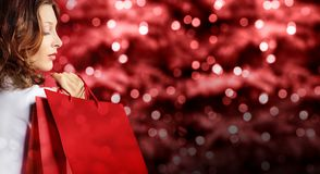 圣诞节购物,有袋子的妇女在红色弄脏了明亮的光 库存照片