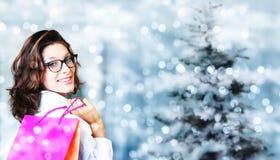 圣诞节购物,有袋子的微笑的妇女在被弄脏的明亮的锂 免版税图库摄影