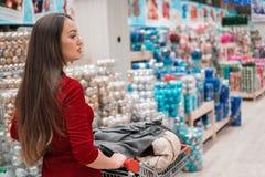 圣诞节购物-有推车的妇女顾客走在超级市场的 库存图片