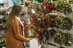 圣诞节购物 装饰的许多,垂悬在商店的圣诞节花圈待售 在女性手上的绿色圣诞节花圈 库存照片