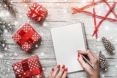 圣诞节贺卡,在白色木背景、手工制造礼物、分支和冷杉球果,红色星 免版税库存照片