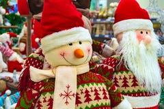 圣诞节软的玩具、雪人和圣诞老人项目 与一个朋友的圣诞老人项目商店挡风玻璃的 免版税库存图片