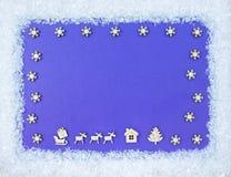 圣诞节辅助部件和鹿框架在蓝色木背景 顶视图 免版税库存照片