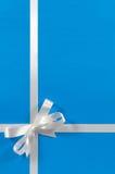 圣诞节边界框架在白色缎,蓝纸背景垂直的礼物丝带 免版税库存图片