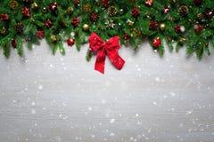 圣诞节边界-冷杉分支和装饰品在木板条与红色丝带 免版税库存照片