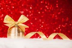圣诞节金球和弓在红色闪烁发光的背景 免版税库存图片