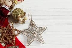 圣诞节金黄星和玩具和红色长袜在白色土气 免版税库存照片