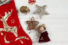 圣诞节金黄玩具和红色长袜在白色土气木b 免版税库存照片