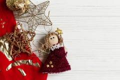 圣诞节金黄玩具和红色长袜在白色土气木b 免版税库存图片