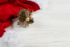 圣诞节金黄装饰品和圣诞老人帽子在白色土气木b 图库摄影