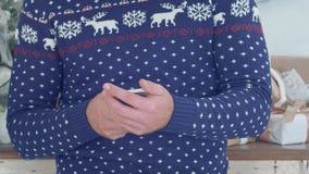 圣诞节针织品的年轻人在他的手上的拿着电话 库存图片
