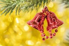 圣诞节铃声在树枝的装饰品吊与黄色bokeh ba 库存图片