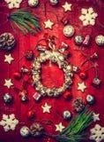 圣诞节铃声花圈、装饰、雪花和冷杉分支在红色木背景 免版税图库摄影