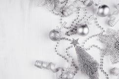 圣诞节银色闪烁装饰-球,卷毛磁带,一品红,在白木委员会的树 免版税库存图片