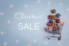 圣诞节销售和购物台车有礼物盒的 库存图片