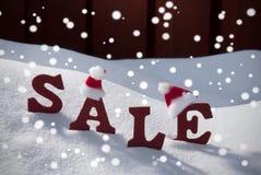 圣诞节销售雪花在雪的圣诞老人帽子 库存照片