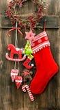 圣诞节长袜和手工制造玩具垂悬 束木被雕刻的装饰葡萄的葡萄酒 免版税库存照片