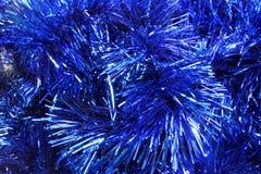 圣诞节闪亮金属片蓝色背景  免版税库存图片