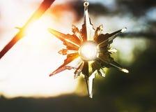 圣诞节闪耀在阳光下在一个室外设置的星装饰品 免版税库存图片