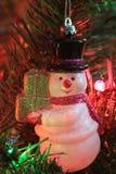 圣诞节雪人射击了在圣诞树的特写镜头 免版税库存图片
