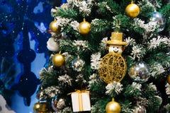 圣诞节雪人,礼物盒,在降雪的圣诞树的中看不中用的物品装饰 免版税库存图片