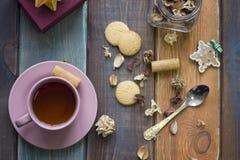 圣诞节静物画用茶、匙子、曲奇饼、一个瓶子干燥花和礼物盒 免版税图库摄影