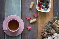 圣诞节静物画用茶、杉木花圈和一碗色的糖果 免版税库存图片