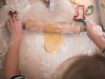 圣诞节面包店:女孩辗压曲奇饼面团 库存图片