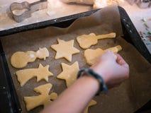 圣诞节面包店:投入曲奇饼面团的不同的形状女孩在一个烘烤的盘子 免版税库存图片