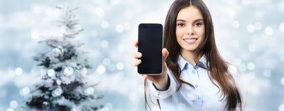 圣诞节题材微笑的妇女显示智能手机,在被弄脏的光 库存图片