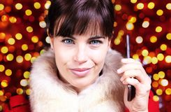 圣诞节题材,使用在被弄脏的brigh的微笑的妇女智能手机 库存图片