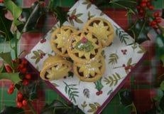 圣诞节食物与传统的摄影图象肉馅饼和新伐霍莉叶子和莓果在绿色红色厨房用桌上 库存照片
