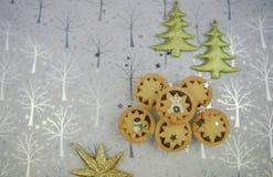 圣诞节食物与季节性的摄影图片与闪烁树和星装饰的肉馅饼在发光的银色背景 免版税库存照片