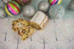 圣诞节食物与欧洲人的摄影图片stollen果子面包蛋糕和五颜六色的中看不中用的物品树装饰在背景中 免版税库存照片