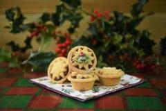 圣诞节食物摄影图片用酥皮点心果子肉馅饼和新伐霍莉叶子和莓果在绿色红色厨房用桌上 库存照片