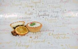圣诞节食物摄影在xmas包装纸背景的肉馅饼和肉桂条橙色果子切片 免版税库存图片