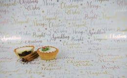 圣诞节食物摄影在xmas包装纸背景的肉馅饼和香料肉桂条 免版税图库摄影