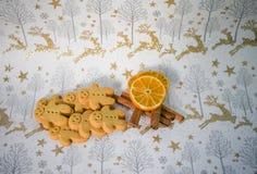 圣诞节食物摄影有香料肉桂条橙色果子切片的姜饼人人在金驯鹿包装纸 免版税库存照片