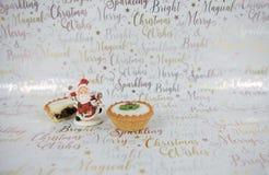 圣诞节食物摄影肉馅饼和装饰xmas包装纸背景的快活的圣诞老人 图库摄影