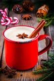 圣诞节饮料:热的白色巧克力用桂香和茴香在红色杯子 库存图片